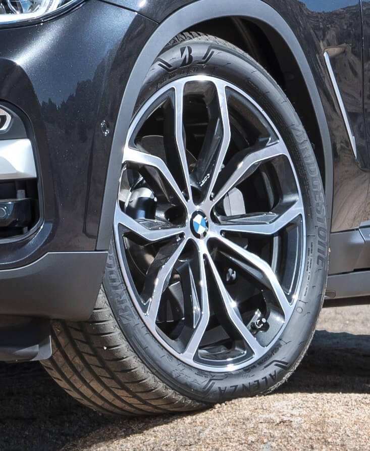 Close up de una llanta Bridgestone en una camioneta negra BMW