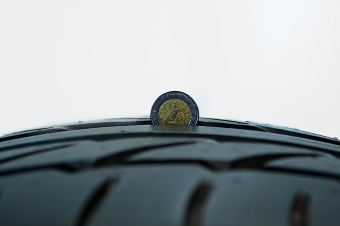 Llanta con una moneda incrustada en una de sus estrías que ilustra su posible desgaste
